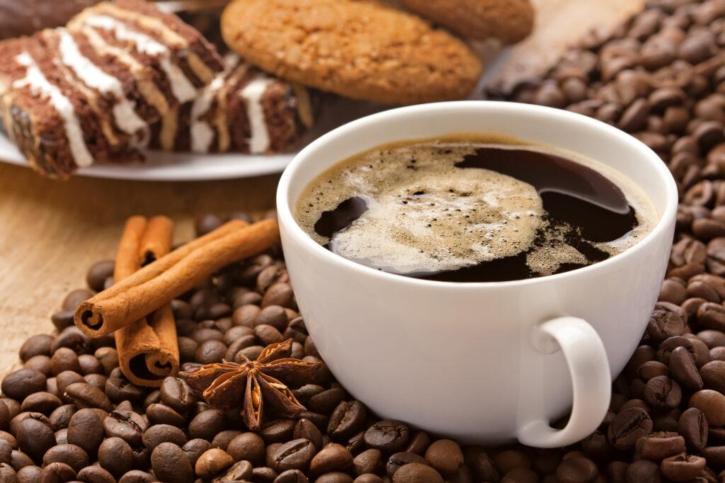 Coffee cup, cinnamon, anise on coffee beans